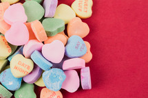 Multi-colored candy hearts with Valentine messages on a red background.