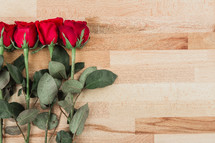 red long stem roses on wood