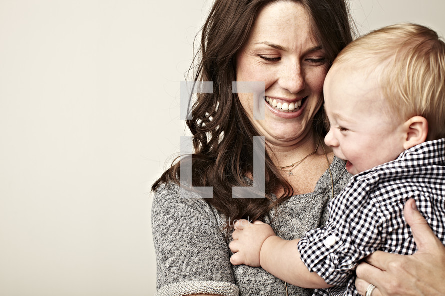 A small boy and his mother hugging and smiling.