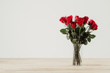 Red roses in a clear glass vase with a white background.