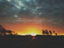 sun setting behind the tree line