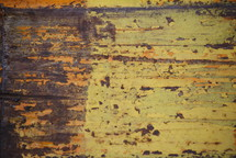 Aged wood with peeling yellow paint.