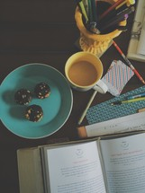 cookies on a plate, open Bible, pens in a cup, coffee mug, and journal on a messy desk