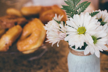 daisies in a vase and donuts