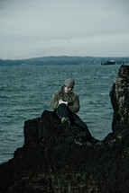 man journaling on a rock along a shoreline