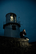 man sitting beneath a lighthouse at night