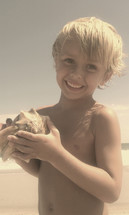 A happy little boy holding a whelk seashell on a beach on a summer day