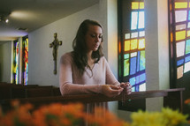 A young woman praying the rosary while kneeling in a Catholic church