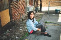 a woman sitting on a curb