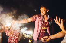 holding sparklers outdoors at night