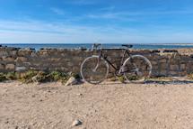 bike leaning against a stone wall on a beach
