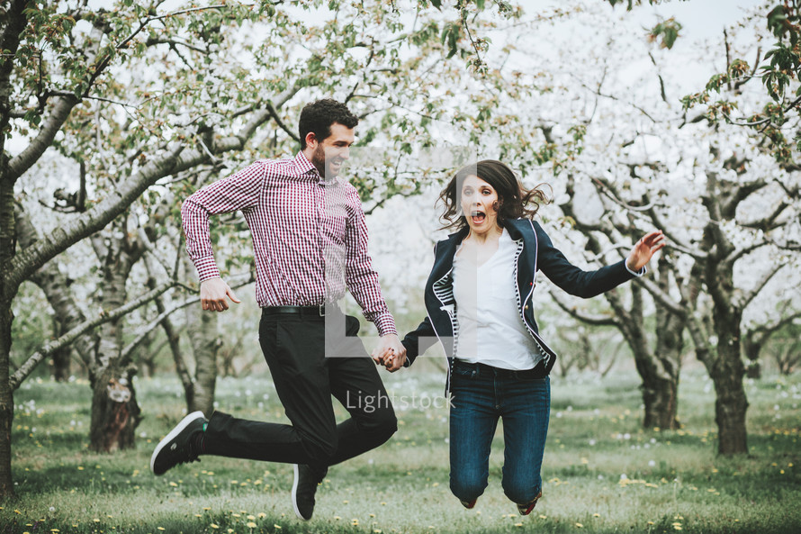 celebrating couple in an orchard