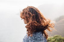 a woman's red hair blowing in the wind