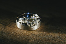 wedding band and engagement ring on a wood table