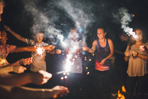 youth holding sparklers outdoors at night