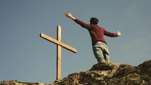 a man standing at the top of a mountain with outstretched arms looking at a cross