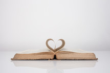 pages of a Bible folding into the shape of a heart