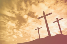 three crosses on a mount at sunrise