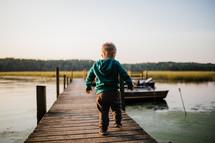 toddler boy walking on a pier