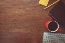 notepad, pencil, journal, coffee mug, keyboard on a desk