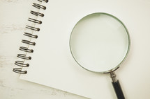 magnifying glass on a blank sketchpad