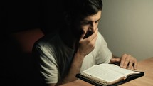 man praying and reading a Bible