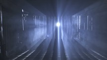 man walking in a dark room with rays of light shining through cracks in the wall