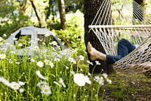 A person reclining on a hammock near a tent feet relaxation camping peace