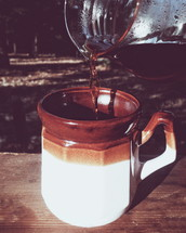 pouring coffee in a mug outdoors