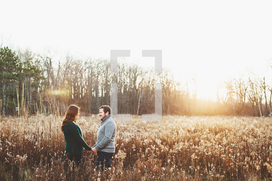 a couple standing in a golden field
