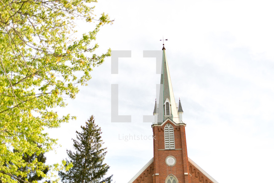 brick church with steeple and spring trees