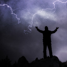 Man praising God in a lightning storm. God is in control of all things. He has power beyond our imagination. Trust in him through all of life's dark moments and you will not be let down.