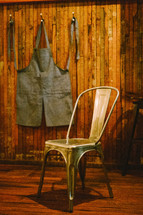 A apron hanging on a hook and a chair.
