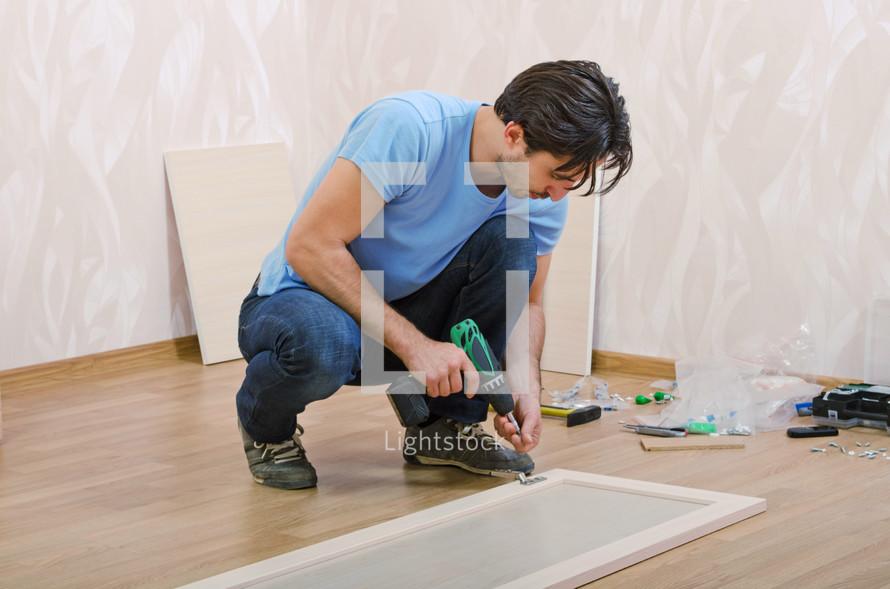 Man assembling furniture on the floor.