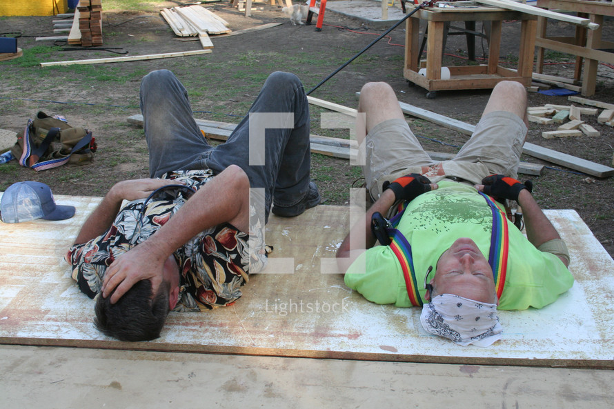 Two exhausted construction workers laying down on a plywood board.