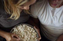 movie night, a couple watching tv together with a big bowl of popcorn