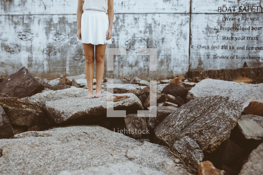 a woman standing on rocks bare foot