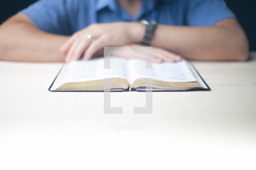 Man reading an open Bible on a table.