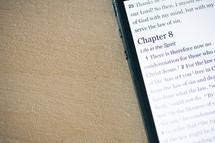 Romans 8 scripture on the screen of a smart phone.