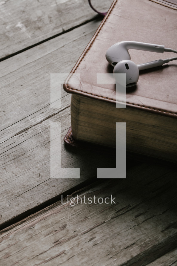 ear buds resting on a Bible