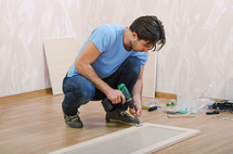 Man assembling furniture on the floor.