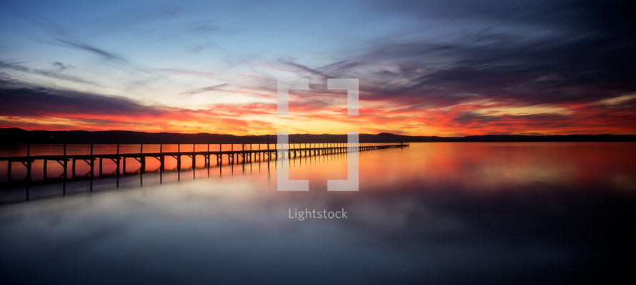 Wooden jetty into the ocean at sunset.