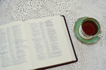 an open Bible and tea cup on a lace table cloth