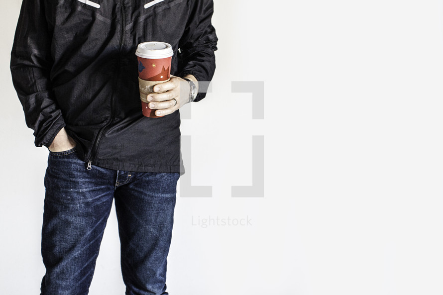 torso of man holding a coffee travel mug