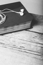 ear buds resting on top of a Bible