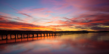 pink sky over a pier at sunset