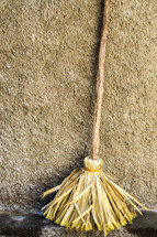 Primitive broom against a  stucco wall