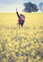 A woman stands in a field of yellow flowers with her hand raised to the sky.
