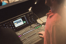 man with his hands on a soundboard