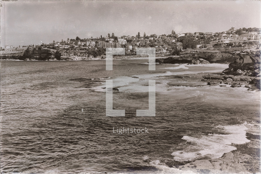 ocean waves and homes along a shoreline